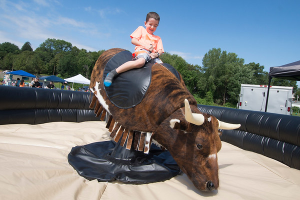 JIM VAIKNORAS/Staff photo Fletcher Hosman, 7, ride the mechanical bull at Merrimac Old Home Day at the Donahue School Saturday morning. The all day event included, face painting, strawberry shortcake, a bike parade, a road race, and much more.