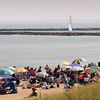 BRYAN EATON/Staff photo. A sailboat heads up the Merrimack River past sun worshippers at Salisbury Beach State Reservation on Monday afternoon. On Sunday around noon, DCR staff were at the entrance of the reservation road informing visitors the parking lots were full and diverting people to the municipal lot and private lots. The beach should be busy this week as the weather is hot with a shower possible then turning dry and sunny.
