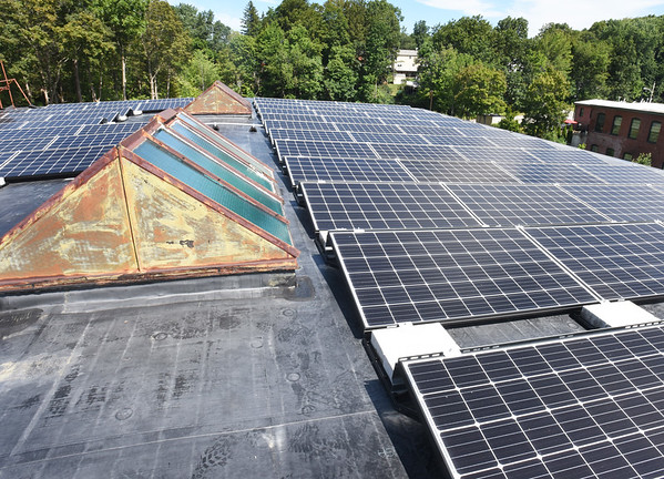 BRYAN EATON/Staff photo. Solar panels top the roof next to old skylights at 14 Cedar Street Studios.