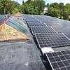 BRYAN EATON/Staff photo. Solar panels top the roof next to old skylights at 14 Cedar Street Studios.