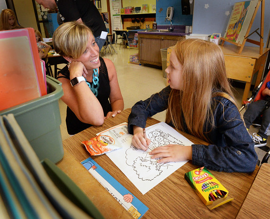 "BRYAN EATON/Staff photo. Keira Ramey, 6, chats with her first grade teacher, Susan Kimball, at Amesbury Elementary School on Tuesday at a ""meet and greet"" where children get their seating assignments and get familiar with their classroom. Classes were to start Wednesday in the Amesbury and Newburyport school systems."