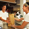BRYAN EATON/Staff photo. Galaxie Story hands Travis Sumner of Newburyport the first order of the day, a dozen bagels, mostly sesame. He won the Newburyport Education Foundation auction and had the honor of being the first customer of the reopened Abraham's Bagels which was was destroyed by fire last June.