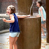 BRYAN EATON/Staff photo. Sisters Ella Johnson, left, 5, and Ava, 8, play in the water fountain on Inn Street in Newburyport on Monday afternoon. They and their family from Haverhill visit Newburyport often.