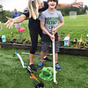 BRYAN EATON/Staff photo. Aide Tracy Johnson cheers as Jackson Killen, 13, knocks a golf ball into one of the holes at the miniature golf course built by special education students at Triton High School.