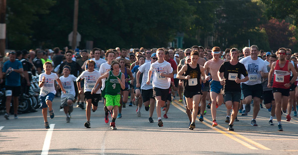 JIM VAIKNORAS/Staff photo Runners take off on State Street at the start of the Newburyport Lions Club 5k Tuesday night.