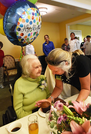 BRYAN EATON/Staff photo. Staffer Jill Ramsdell presents Atria Merrimack Place resident Clara Sillars with her favorite flavored cupcake: chocolate, though there was a bigger cake in the wings. Sillars, who was born in Danvers, turned 107 years-old yesterday and was feted by staff and local polititians.