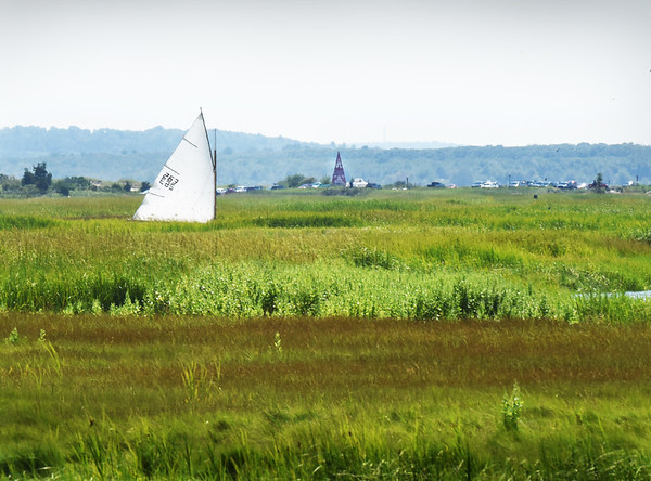 BRYAN EATON/Staff photo. A sailboat seems to be stranded in the marsh at Salisbury Beach State Reservation on Wednesday afternoon. It was actually being sailed expertly through the extremely meandering Black Rock Creek back to the Merrimack RIver. The navigational aid, Ben Butler's Toothpick, can be seen to the right of the vessel.