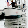 BRYAN EATON/Staff photo. With three people on board, captain Bill Taplin checks his watch for his 4:30 tour on Tuesday afternoon on his boat Coastie. He takes people to tour the Merrimack River upriver to Amesbury past Lowell's Boat Shop and while these people were waiting pointed out a seal that was jumping up for fish.
