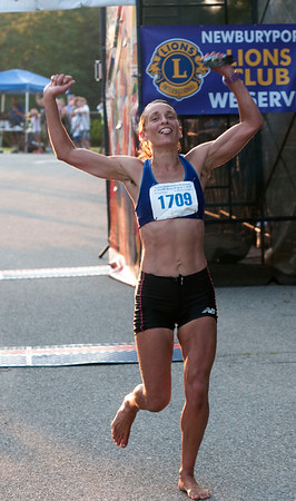 JIM VAIKNORAS/Staff photo First female Apryl Sabadosa crosses the finish line at the Newburyport Lions Club 10 mile race.