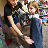 BRYAN EATON/Staff photo. Former student, and now assistant at Colorful Kids Adelaide Saltsman, 13, fits Amelia Hopp, 6, with a costume as she's playing a maid in a medieval play they're producing.