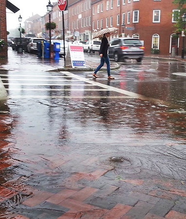 BRYAN EATON/Staff photo. A burst of rain caused some minor flooding in Newburyport's Market Square at noon on Wednesday as it rained on occasion throughout the day. The rain is forecast to break this morning with generally nice weather for the weekend.