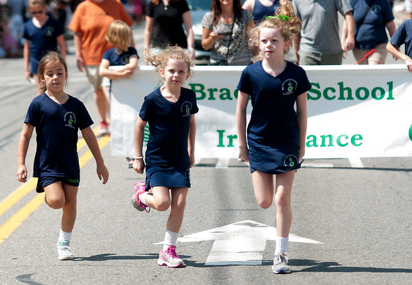 JIM VAIKNORAS/Staff photo. Brook McCarron,7, Ciara McCarthy,7, and Maeve McCarthy, 9, from the Bracken School of Irish Dance step their way down High Street during the Yankee Homecoming Parade