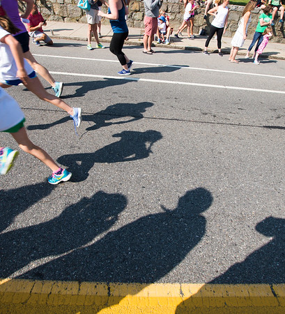 JIM VAIKNORAS/Staff photo Runners cast long shadow Sunday morning in High Street Mile in front of Newburyport High School.