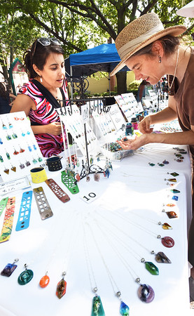 BRYAN EATON/Staff photo. Jessie Brown of Arlington, right, checks out the handmade jewelry by Carolina Portillo of Melrose at the Inn Street Artisan's Revival.