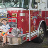AMANDA SABGA/Staff photo<br /> <br /> Gabriel Zapata, 2, of Amesbury poses on a Newburyport fire truck during Yankee Homecoming's Family Day at Maudslay State Park in Newburyport.<br /> <br /> 8/3/19