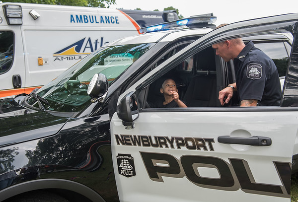 AMANDA SABGA/Staff photo<br /> <br /> Audreas Desir, 4, of Epping explores a Newburyport Police car with OfficerEric Andrukaitis during Yankee Homecoming's Family Day at Maudslay State Park in Newburyport.<br /> <br /> 8/3/19