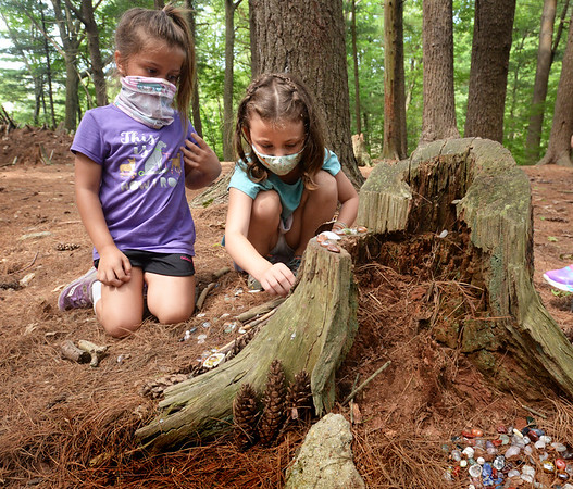 BRYAN EATON/Staff Photo. Quinn Welch, left, and Gwen Moell, both 6, build a fairy hous using glass rocks, bark and twigs on an old pine stump. They were in one of the Amesbury Youth Recreation programs at Camp Kent on Lake Gardner.