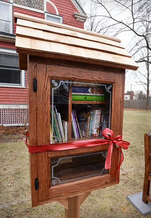 BRYAN EATON/Staff photo. Katie Johnson has finished her little library and is now open for business at the corner of Elm Street and Goss Avenue in Amesbury.
