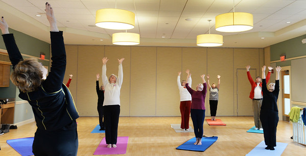 BRYAN EATON/Staff photo. Yoga teacher Mary Van Abs, left, leads a yoga class at the Newburyport Senior Center. She gives the class every Thursday at 2:30 p.m. and works with the participants with whatever their needs are.