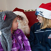JIM VAIKNORAS/Staff photo Olivia Bub, 4, and her sister Hannah, 8, of Groveland have a chat with Santa at his workshop on Inn Street in Newburyport Sunday. Olivia wants a Giggle wiggle Game and Hannah wants a Fitbit.