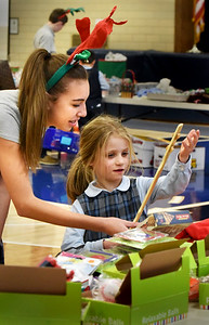 BRYAN EATON/Staff photo. First-grader Kami Christie, 6, gets help from eighth-grader Gabby Riethmueller, 13, to choose gifts at the Immaculate Conception School's Christmas Store on Monday afternoon. The younger students are hooked up with older students to mentor them in which gifts may be appropriate for family members and friends, and make sure they don't go over their spending limit as they learn to budget.