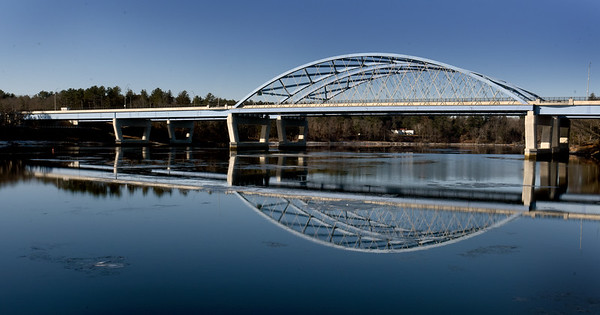 BRYAN EATON/Staff photo. The Whittier Bridge reflects on a very calm Merrimack River in photo taken from Deer Island on Tuesday morning. The Chailey Estate at the end of Spring Lane in Newburyport can be seen under the suspension span.