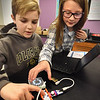 BRYAN EATON/Staff photo. Molin Upper Elementary School students Grant Cooper, left, and Lily DeJordy, both 11, work on a coding project in Kristen Daigle's class programming an LED matrix, pictured under her hand.