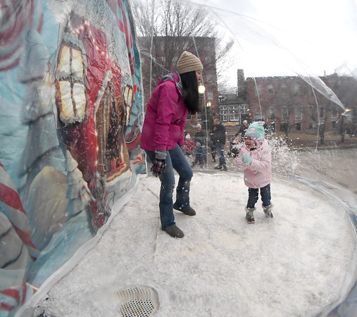 JIM VAIKNORAS/Staff photo Madison Blair, 3, and her mm Candice have a snowball figh inside a giant snowglobe at the Al Capp Theater at Amesbury's Winterfest Sunday afternoon.