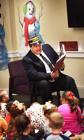 """BRYAN EATON/Staff photo. Jim Poulin plays the conductor as he reads """"The Polar Express"""" sponsored by Family Connections and the Salisbury Public Library where the event was held on Tuesday night. There was surprise visit by Santa Claus for the children who arrived with a police and fire department escort."""