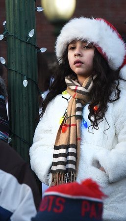 BRYAN EATON/Staff photo. Wearing a Santa Claus hat and Christmas lights around her neck, Carmilla Maldondo, 6, waits to see St. Nick in the Amesbury Santa Parade.