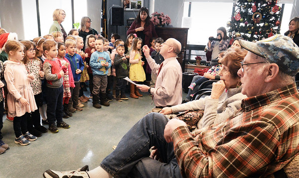 """BRYAN EATON/Staff photo. Amesbury Elementary School Principal Walter Helliesen leads kindergartens in """"Rudolph The Red-Nosed Reindeer"""" on Wednesday morning. The kindergarters have been coming to the Amesbury Senior Center for several years now singing Christmas and seasonal songs."""
