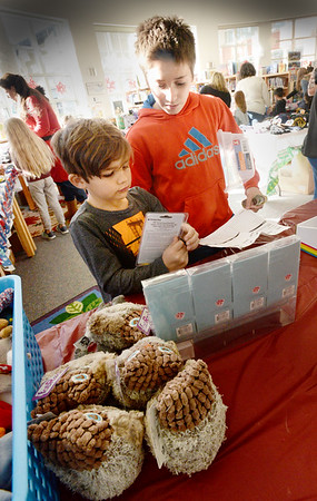 BRYAN EATON/Staff photo. Jacob Scagel, 11, right, looks on as Jackson Modini, 5, looks over gifts as he shops for family at the Holiday Shop at the Salisbury Elementary School on Tuesday. Sponsored by the school's PTA as a fundraiser, it pairs older students with younger ones to give advice about what gifts may be good for which family member, how to budget and add up their costs to make sure they're within that budget.