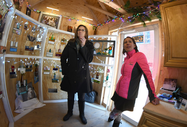 JIM VAIKORAS/Staff photo Stain glass artist Kristine Arnold, and Darlene Woodward of Pant the Town pet photographer look over there pop up shop at the Newburyport Artisan Winter Village and Workshop at Patrick Tracey Place in Newburyport Saturday.