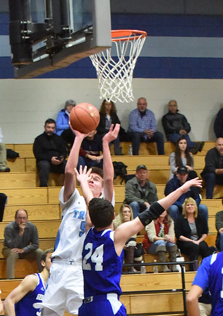 BRYAN EATON/Staff photo. Triton's Max McKensie shoots as Brendan Willis covers.