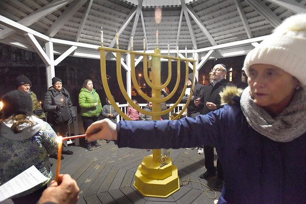 BRYAN EATON/Staff photo. Rabbi Zalman Borenstein of Anshe Sholom Chabad of Greater Haverhill oversaw the grand lighting of the Brave Maccabees of Amesbury's menorah Wednesday night attended by Mayor Ken Gray, his wife Donna, and state Rep. James Kelcourse. Event founder Rachel Barcelona also unfurled the flag of Israel to commemorate the country's 70th birthday.