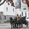 JIM VAIKNORAS/Staff photo A horse drawn carriage from Charming Fare Farm makes it's way past the library at Amesbury's Winterfest Sunday afternoon.