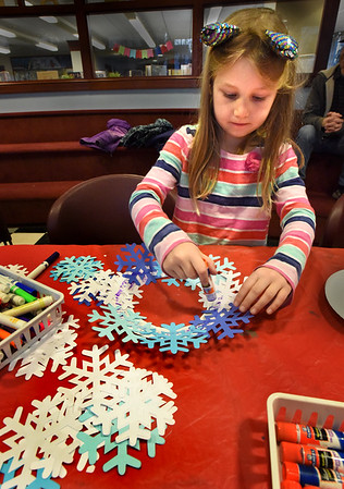 """BRYAN EATON/Staff photo. Serenity Rupp, 6, of Newbury works on a """"winter wreath"""" in the Children's Room of the Newburyport Public Library where they supplied the snowflakes and cut-out plates and glue. She was there with her two sisters Fall, 9, and Tanndria, 5, and also made crowns out of the snowflake cut-outs."""