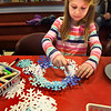 "BRYAN EATON/Staff photo. Serenity Rupp, 6, of Newbury works on a ""winter wreath"" in the Children's Room of the Newburyport Public Library where they supplied the snowflakes and cut-out plates and glue. She was there with her two sisters Fall, 9, and Tanndria, 5, and also made crowns out of the snowflake cut-outs."