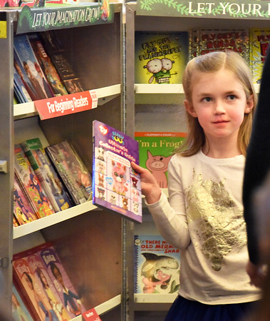 "BRYAN EATON/Staff photo. First-grader Caela Farrell, 6, looks for approval from her teacher Chrissy Platt as one of the books she chose ""Beanie Boos: Ultimate Collector's Guide."" She was at the Bresnahan School's Scholastic Book Fair which raises money to buy new library books."