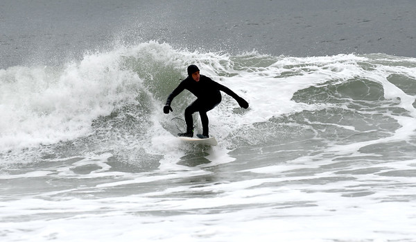 JIM VAIKNORAS/Staff photo John Reynolds rides a wave of Salisbury Beach Saturday afternoon. The high surf was caused by resent storms in the Atlantic.