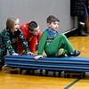 JIM VAIKNORAS/Staff photo Kindergarteners Jax Langmaid and Charlie Zinck push classmate  Matteo Frizzo in the annual Reindeer Races at Salisbury Elementary School Friday afternoon. Teams of 3 took turns pushing and riding on gym mats on top of carts with wheel in the school gym.