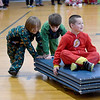 JIM VAIKNORAS/Staff photo Kindergarteners Jax Langmaid and Matteo Frizzo push classmate Charlie Zinck  in the annual Reindeer Races at Salisbury Elementary School Friday afternoon. Teams of 3 took turns pushing and riding on gym mats on top of carts with wheel in the school gym.