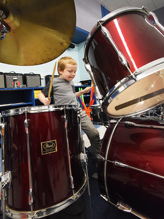 BRYAN EATON/Staff photo. Sean Choquette, 8, jumps in on a drum set at the Boys and Girls Club before the start of lessons. The club is offering the percussion lessons by Tomas Havrda.