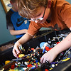 BRYAN EATON/Staff photo. Lucas Zepf, 10, looks through a box of Lego's in the game room at the Boys and Girls Club in Salisbury on Thursday. He was searching for pieces to make a robotic troll.