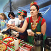 "BRYAN EATON/Staff photo. ""Head Elf"" and Amesbury Middle School teacher Emi Burrell hands out a candy can with hot chocolate as students, from left, Lidya Bellanger, Ramona Sim and Aidan Whittier, all 13, sell cookies. Amesbury Middle School Interact and Peer Leaders were hosting a fundraising event Thursday to benefit the Pettengill House by selling the hot chocolate and cookies during lunch."