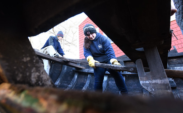 BRYAN EATON/Staff photo. Kovas Saffo, 17, of Merrimac, left, and Molly MacInnis, 18, of Georgetown help to remove a semi-rotted board from the bottom of the shallop which will be replaced.