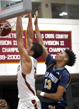 JIM VAIKNORAS/Staff photo Newburyport's Casey McLaren dunks the ball while covered by Jaquan Stroud during the Clippers game against New Mission at Newburyport Friday night.