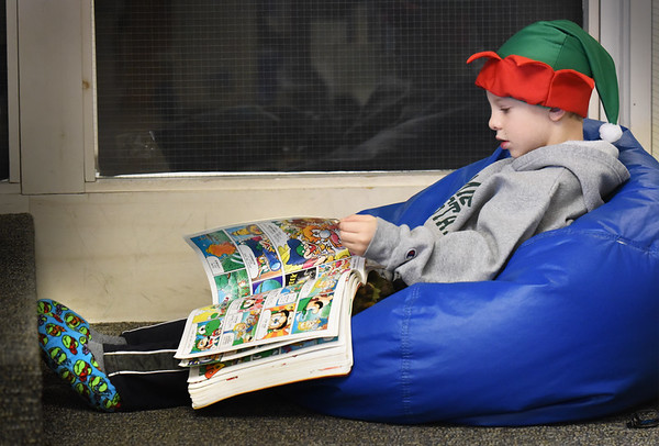 """BRYAN EATON/Staff photo. Wearing an elf hat and slippers, Jackson Gadsby, 6, reads """"Super Mario Adventures"""" settled down in a bean bag chair at Amesbury Elementary School. Librarian Peg Crissinger reads a story to the first-graders on their weekly visit, then they choose books to take home, and if they have time they settle down to read in the loft."""