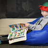"BRYAN EATON/Staff photo. Wearing an elf hat and slippers, Jackson Gadsby, 6, reads ""Super Mario Adventures"" settled down in a bean bag chair at Amesbury Elementary School. Librarian Peg Crissinger reads a story to the first-graders on their weekly visit, then they choose books to take home, and if they have time they settle down to read in the loft."