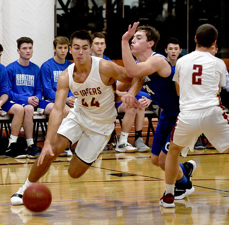 JIM VAIKNORAS/Staff photo Newburyport's Parker McLaren drives past off a screen by teammate Max Gagnon against Georgetown at the Rowinski Holiday Tournament championship game at Newburyport High School Friday night.
